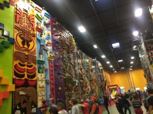 Photo of ClimbZone, a kids' indoor climbing gym. Multiple painted routes with different designs are on walls.