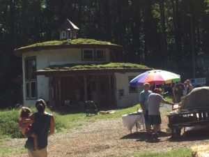 Photo of straw bale house with white paint and green roof