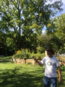 Photo of a white man standing in front of a garden, talking