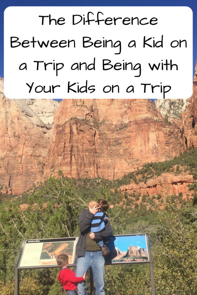 The Difference Between Being a Kid on a Trip and Being with Your Kids on a Trip. (Photo: White man holding one child with his arm around him and holding the hand of another child facing away from the camera in front of red cliffs.)