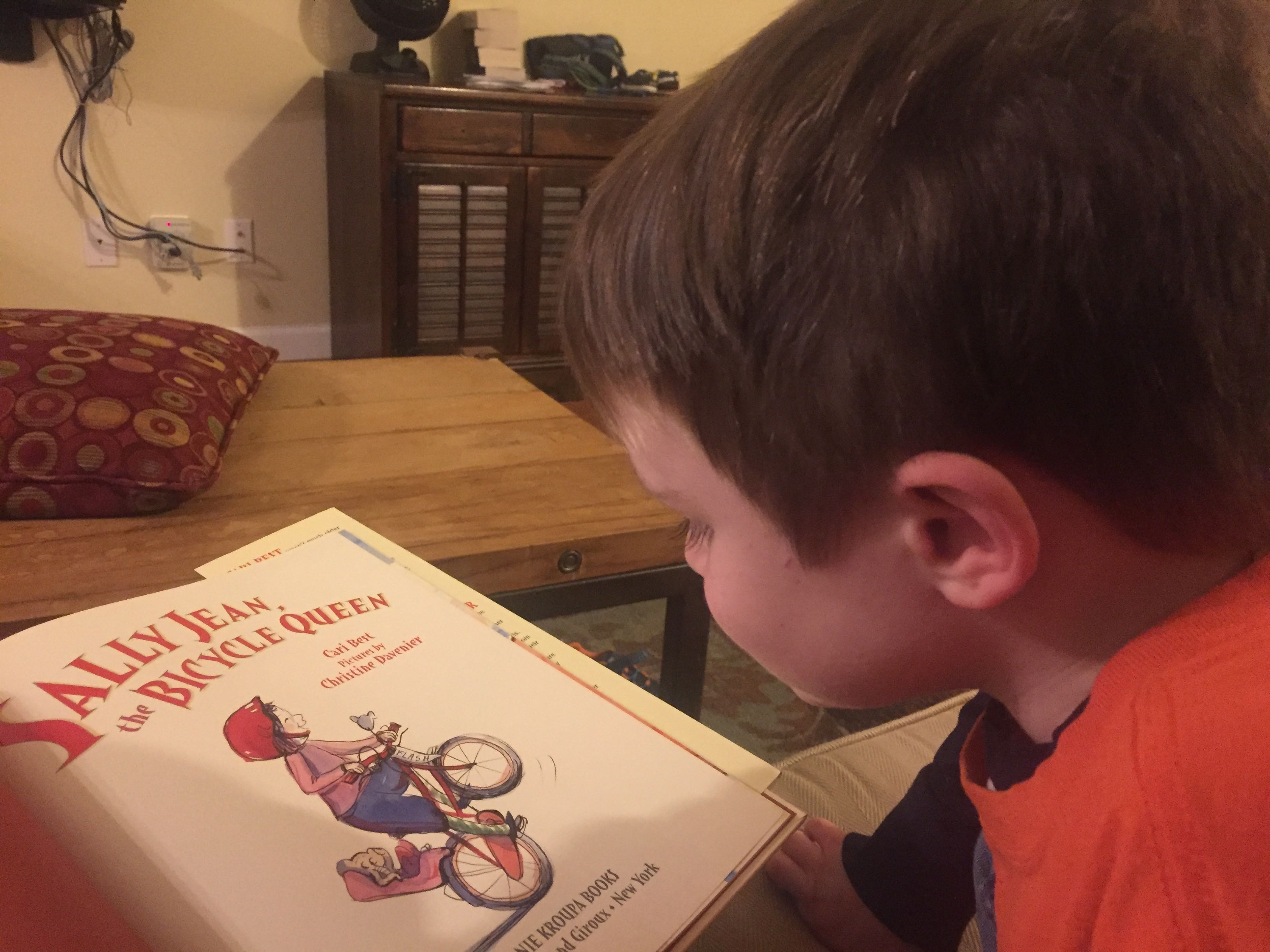 Four-year-old white boy reading a book with a girl on a bicycle on the front.