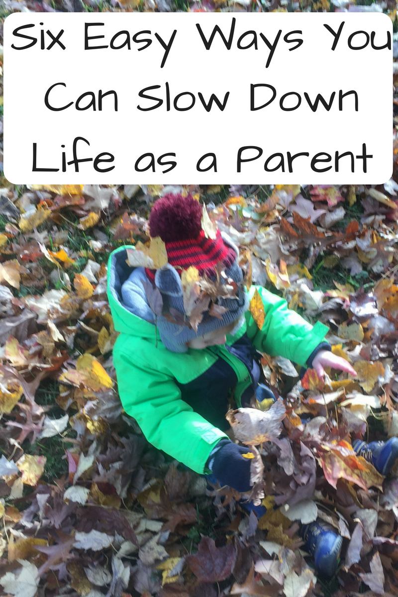 Six Easy Ways that You Can Slow Down Life as a Parent (Photo: Kid with a hat and green jacket sitting in leaves)