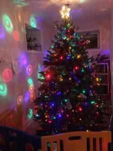 Christmas tree with colored lights shining on wall.