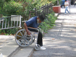 Photo of a black man in a wheelchair moving the wheelchair down stairs