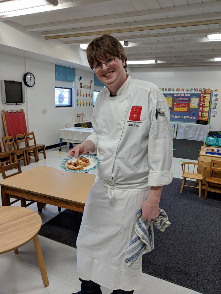 White man in a white chef's jacket in a classroom, holding a piece of French bread pizza