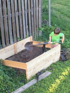Photo of a white child digging with a very large shovel in a raised bed