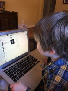 Photo of young white boy with a computer, looking at it playing Piano Man