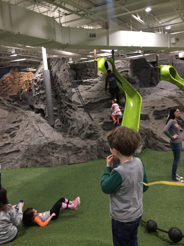 Young white boy looking at a large artificial mountain with green slides coming down the front of it